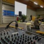 Die Aufgabe für GWH Event Engineering ist in diesem Fall, eine Lagerhalle in einen Kongresssaal zu verwandeln. Bühne, Tontechnik und auch Videotechnik kommen aus unserem Sortiment.